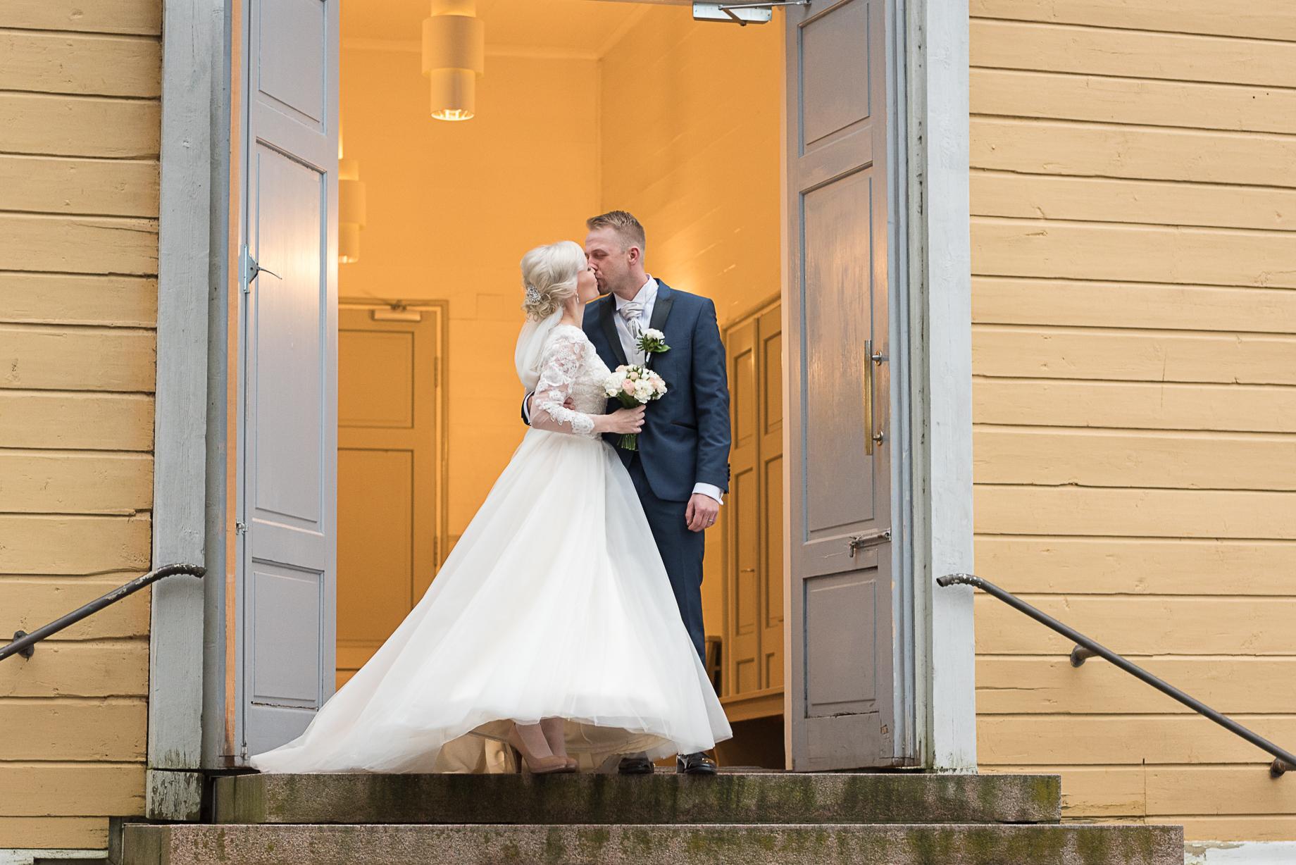 Vihkiparin suudelma kirkon portailla