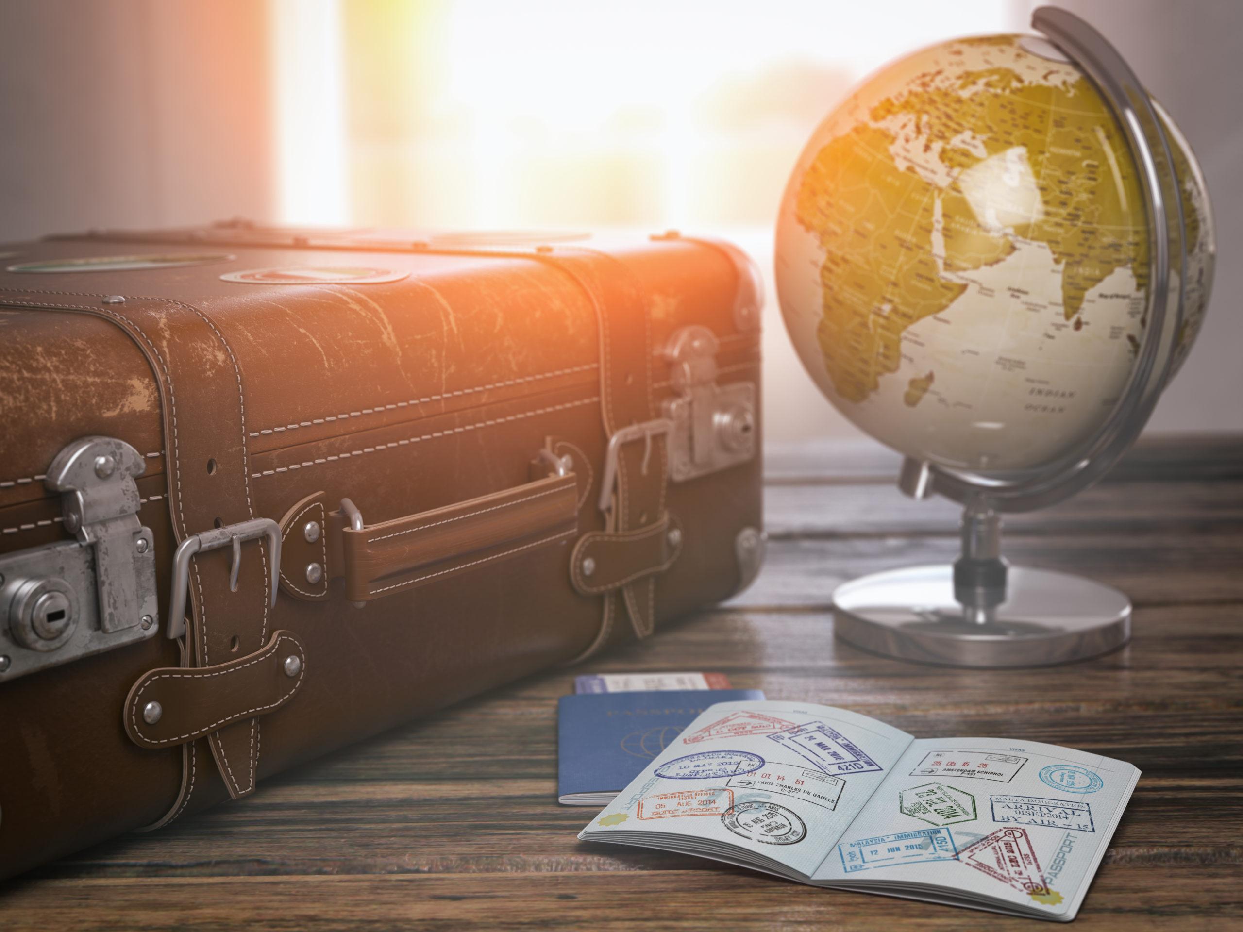 Passi, matkalaukku ja karttapallo